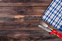 Blue checkered tablecloth on the black wooden table with copy space for your text. Top view.  Royalty Free Stock Photos