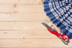Blue checkered tablecloth with knife and fork on a light wooden table with copy space for your text. Top view Royalty Free Stock Images