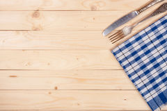 Blue checkered tablecloth with knife and fork on a light wooden table with copy space for your text. Top view.  Royalty Free Stock Photography