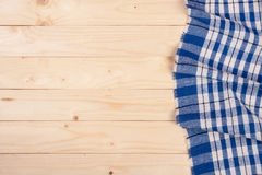 Blue checkered tablecloth on a light wooden table with copy space for your text. Top view.  Stock Image
