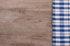 Blue checkered tablecloth on an old wooden table with copy space for your text. Top view Royalty Free Stock Images