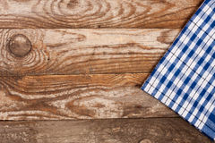 Blue checkered tablecloth on the old wooden table with copy space for your text. Top view Royalty Free Stock Images