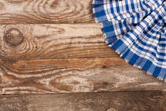 Blue checkered tablecloth on the old wooden table with copy space for your text. Top view.  Royalty Free Stock Photography
