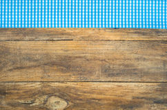 Blue checkered tablecloth on rustic wooden table. Wooden background with blue checkered fabric border Stock Image