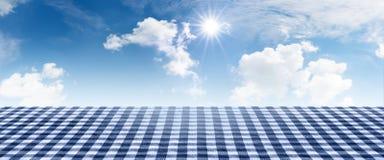 Blue checkered tablecloth with summer sky Stock Photos