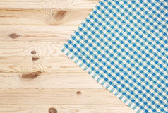 Blue checkered tablecloth on wooden table Stock Images