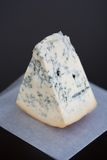 Blue Cheese. Soft Focus Aged Mountain blue cheese wedge on wax paper on a table Royalty Free Stock Images