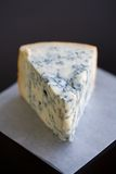 Blue Cheese. Soft Focus Aged Mountain blue cheese wedge on wax paper on a table Stock Photography