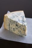 Blue Cheese. Aged Mountain blue cheese wedge on wax paper on a table Royalty Free Stock Photo
