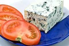 Blue cheese. Closeup of blue cheese and tomato slices on the plate Royalty Free Stock Photo