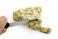 Blue cheese being cut over white Royalty Free Stock Images