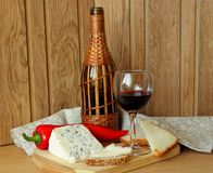Blue cheese, a bottle and a glass of wine. Still life with wine and cheese Royalty Free Stock Photography
