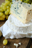 Blue cheese and camembert on a background of grape Stock Photos