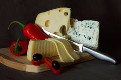 Blue cheese,cheese with holes, red pepper and knife Royalty Free Stock Image