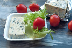 Blue cheese, cherry tomatoes and fresh salad leaves on a wooden surface Stock Image