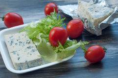 Blue cheese, cherry tomatoes and fresh salad leaves on a wooden surface Stock Photography