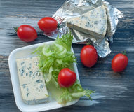 Blue cheese, cherry tomatoes and fresh salad leaves on a wooden surface Royalty Free Stock Photos