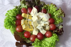 blue cheese close up with grapes and salad on table Royalty Free Stock Images