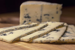 Blue cheese close up on an old wooden board and a knife Selective focus Royalty Free Stock Image