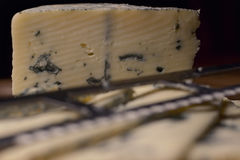 Blue cheese close up on an old wooden board and a knife Selective focus Stock Photo