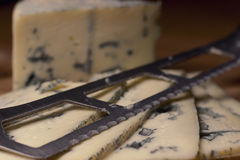 Blue cheese close up on an old wooden board and a knife Selective focus Stock Photos