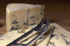 Blue cheese close up on an old wooden board and a knife Selective focus Royalty Free Stock Photography