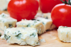 Blue Cheese Closeup. Danish blue cheese closeup with tomatoes in the background Royalty Free Stock Photo