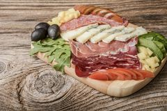 Blue cheese and cold meat platter with salami, slices ham prosciutto, cheese, olives and herbs. On wooden background Stock Image