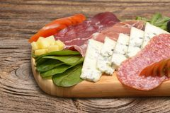 Blue cheese and cold meat platter with salami, slices ham prosciutto, cheese, olives and herbs. On wooden background Stock Photos