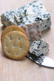Blue Cheese And Crackers. Blue cheese with crackers and knife on wooden board Royalty Free Stock Photo