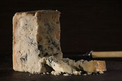 Blue Cheese Dark. Blue cheese on a wooden board with a dark background royalty free stock photography