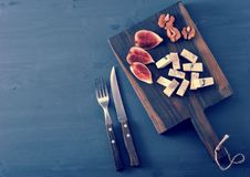 Blue cheese, fresh figs and walnuts on a wooden Board and a knif. E and fork on a black wooden rustic background - top view Stock Image