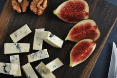 Blue cheese, fresh figs and walnuts on a wooden Board and a knif. E and fork on a black wooden rustic background - top view - closeup Royalty Free Stock Photos