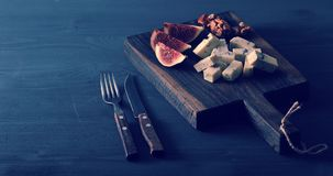 Blue cheese, fresh figs and walnuts on a wooden Board and a knif. E and fork on a black wooden rustic background Royalty Free Stock Photography