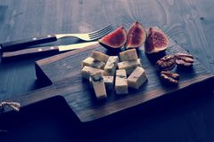 Blue cheese, fresh figs and walnuts on a wooden Board and a knif. E and fork on a black wooden rustic background Royalty Free Stock Image