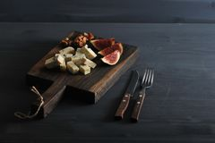 Blue cheese, fresh figs and walnuts on a wooden Board and a knif. E and fork on a black wooden rustic background Royalty Free Stock Photos