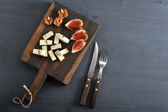 Blue cheese, fresh figs and walnuts on a wooden Board and a knif. E and fork on a black wooden rustic background Stock Images