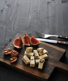 Blue cheese, fresh figs and walnuts on a wooden Board and a knif. E and fork on a black wooden rustic background Stock Image