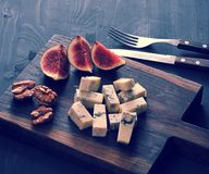 Blue cheese, fresh figs and walnuts on a wooden Board and a knif. E and fork on a black wooden rustic background Stock Photo