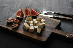 Blue cheese, fresh figs and walnuts on a wooden Board and a knif. E and fork on a black wooden rustic background Royalty Free Stock Photo