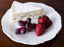 Blue cheese and fresh fruits. A slice of creamy French blue cheese on a saucer with fresh strawberries and grapes royalty free stock images