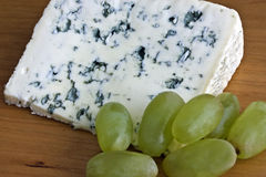 Blue cheese and grapes. A slice of creamy blue cheese with a small bunch of grapes, on a wooden board stock images