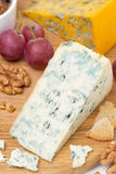 Blue cheese, grapes, crackers, jam and nuts on a wooden board Royalty Free Stock Photos