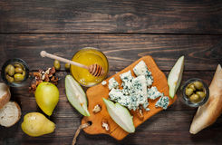 Blue cheese with honey, olive and pears on rustic table. Text place Stock Images