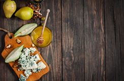 Blue cheese with honey, olive and pears on rustic table. Text place Stock Image