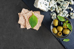 Blue cheese with olive, basil and crispbread Royalty Free Stock Images