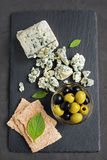 Blue cheese with olive, basil and crispbread Stock Photo