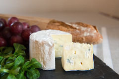 Blue cheese on a plate with grapes. Royalty Free Stock Image