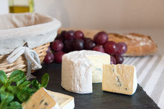 Blue cheese on a plate with grapes. Royalty Free Stock Images