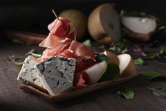 Blue cheese with prosciutto , pear and spinach. Stock Images